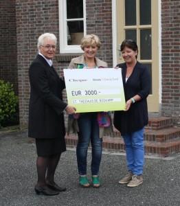 Marga Haveman van Monuta Haveman overhandigt de cheque aan secretaris Marga Komen en voorzitter Petra de Kruijf van Stichting Theehuis De Boskamp.